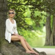 Attractive blonde sitting on roots of tree — Stock Photo #76618045
