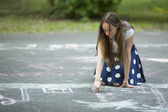 Lovely teen girl draws with chalk — Stock Photo