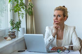 Business woman pensively sits with laptop — Stock Photo