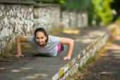 Young sporty woman doing push-ups — Stock Photo