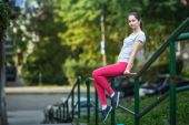 Young sporty woman sitting on railing — Stock Photo