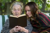 Elderly woman reading  book with granddaughter. — Stock Photo