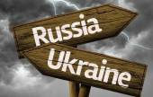Russia and Ukraine wooden sign on a bad weather — Stock Photo