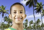Little Brazilian boy smiling in tropical background — Stock Photo