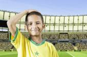 Brazilian little boy putting his hand on his head in the stadium — Stock Photo