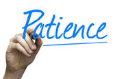 Patience hand writing with a blue mark on a transparent board — Stock Photo