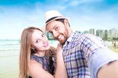 Beautiful couple taking a selfie photo in the beach — Stockfoto