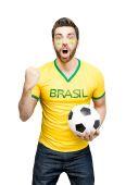 Brazilian fan holding a soccer ball celebrates — Stock fotografie