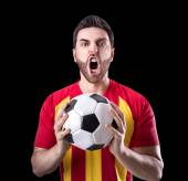Fan on red and yellow uniform celebrates on black background — Stock Photo