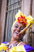 Portrait of african cuban woman smoking cigar and looking at camera smiling — Stock Photo