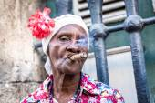 Portrait of african cuban woman smoking cigar and looking at camera — Stock Photo