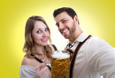 Couple in traditional bavarian costume on yellow background — Stock Photo