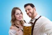 Couple in traditional bavarian costume on blue background — Stock Photo