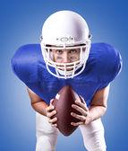 Football Player on blue uniform on blue background — Stock Photo