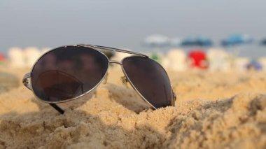 Точек, лежащих на песке. В солнцезащитные очки отражение солнца, неба и человека — Стоковое видео