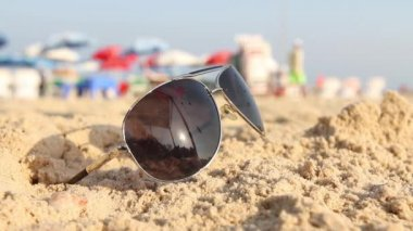 Points lying on the sand. In the sunglasses reflected the sun, sky and the human — Stock Video