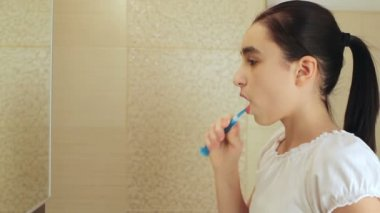 Cute little girl intensely brushing her teeth — Stock Video