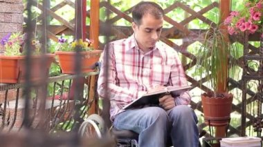 Young man in wheelchair reading — ストックビデオ