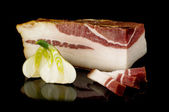 Smoked pork fat or salo on the dark reflective surface — Stock Photo
