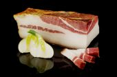 Smoked pork fat or salo on the black reflective surface — Stock Photo