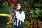 Mysterious woman in Victorian dress among the autumn leaves — Stock Photo