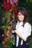 Mysterious woman in Victorian dress among the autumn leaves — Foto de Stock