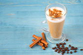 Cafe latte and coffee beans and cinnamon — Stock Photo