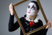 Woman in disguise harlequin in the picture frame — Stock Photo