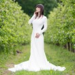 Woman in a white dress in the orchard — Stock Photo #76167043