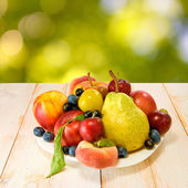 Various ripe fruits on a plate on a blurred background — Stock Photo