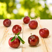 Plums on green background — Stock Photo
