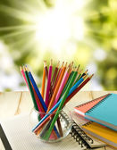 Notebook and pencil on green background  — Stock Photo
