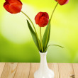 Three flowers tulips in a vase on a green  background closeup — Stock Photo #68076857