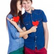 Beautiful young couple holding a small red paper heart in hands — Stock Photo #65324441