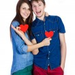 Beautiful young couple holding a small red paper heart in hands — Stock Photo #65324521
