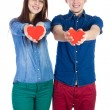 Beautiful young couple holding a small red paper heart in hands — Stock Photo #65324533