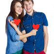 Beautiful young couple holding a small red paper heart in hands — Stock Photo #65324537