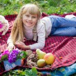 Beautiful little young baby lies on a red plaid. Lovely  child smiling with bright flowers — Stock Photo #66912547