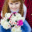 Beautiful little young baby sitting  on a red plaid. Lovely  child smiling with bright flowers — Stock Photo #66914725