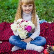 Beautiful little young baby sitting  on a red plaid. Lovely  child smiling with bright flowers — Stock Photo #66914735