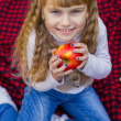 Beautiful little young baby in a pink hat with an apple in his hand. Beautiful child sitting on a red plaid. — Stock Photo #66915429