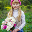 Beautiful little young baby in a pink hat with flowers in their hands — Stock Photo #66916169