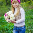 Beautiful little young baby in a pink hat with flowers in their hands — Stock Photo #66916349
