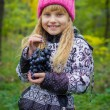 Beautiful little young baby in a pink hat with grapes in their hands — Stock Photo #66916863