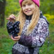 Beautiful little young baby in a pink hat with grapes in their hands — Stock Photo #66916873