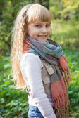 Beautiful little young baby stands in a scarf. Lovely  child smiling — Stock Photo