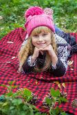 Lindo pequeno bebê jovem de chapéu-de-rosa. Linda criança encontra-se em uma manta vermelha — Fotografia Stock