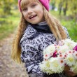 Beautiful little young baby in a pink hat with flowers in their hands — Stock Photo #66920083