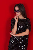 Beautiful brunette girl in a black dress and sunglasses. Brunette with long black hair — Stock Photo