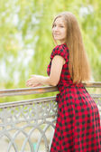 Doğada uzun kahverengi saçlı güzel bir genç kadının portresi. balkonda ekose bir elbise poz kız. — Stok fotoğraf